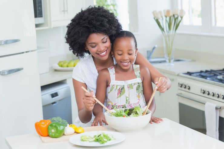 46070960 - mother and daughter making a salad together at home in the kitchen